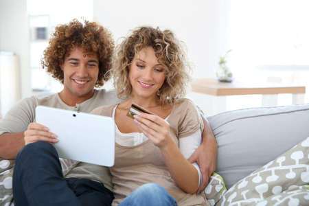 Cheerful couple at home e-shopping with tablet Imagens - 25224394