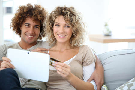 Cheerful couple at home e-shopping with tablet photo