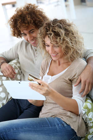 secured payment: Cheerful couple at home e-shopping with tablet Stock Photo