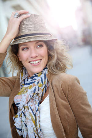 Cheerful blond woman in town with hat on photo
