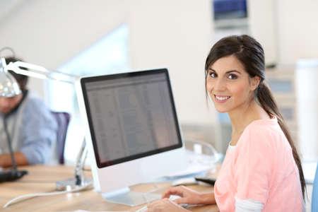 Beautiful girl sitting in office in front of desktop photo