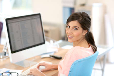 Beautiful girl sitting in office in front of desktop Stock Photo