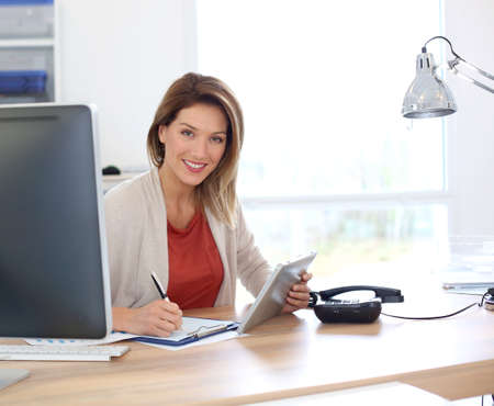 smiling women: Businesswoman in office working with tablet
