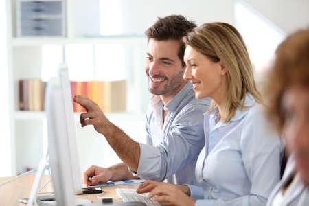 workteam: Workteam in office working on desktop computer Stock Photo