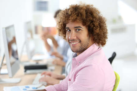 officeworker: Smiling office-worker sitting at desk