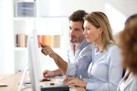 Werkgroepen in het kantoor werken op desktop computer Stockfoto