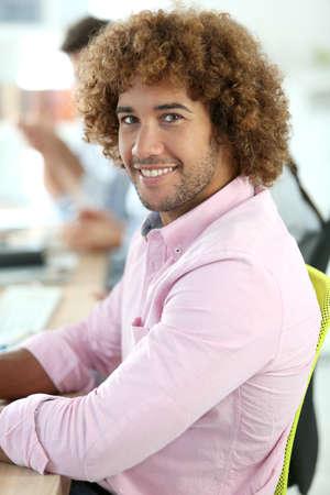 officeworker: Smiling office-worker sitting at desk