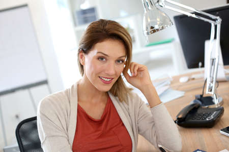 Successful businesswoman sitting at desk in office photo
