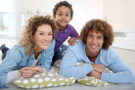 mixed family: Happy family laying down the floor at home