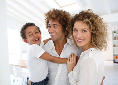 mixed ethnicities: Happy family standing in brand new home Stock Photo