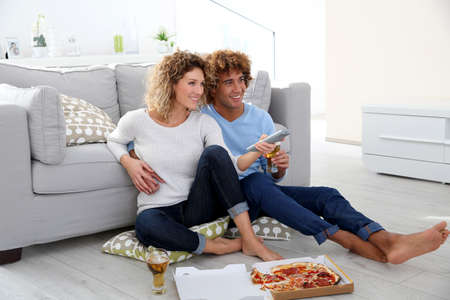 Cheerful couple at home having pizza in font of TV photo