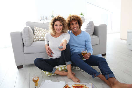 Pareja alegre en casa con la pizza en la fuente de TV photo