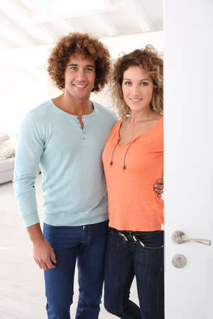 Cheerful couple opening new home entrance door photo