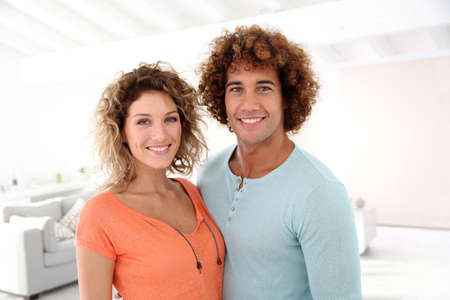 mixed race ethnicity: Cheerful couple standing in their new place Stock Photo
