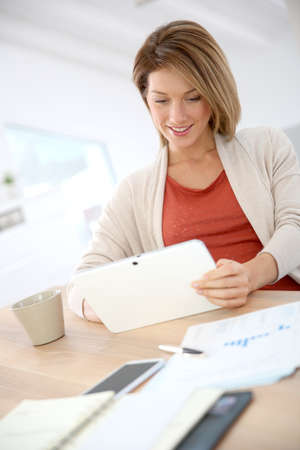 telework: Woman working from home on digital tablet