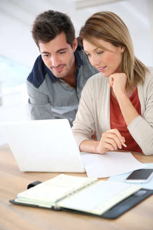 Couple at home checking accounts on internet photo