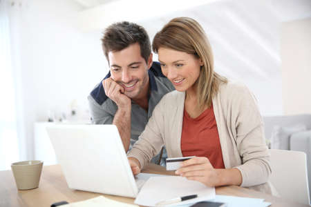 Couple at home buying on internet Imagens