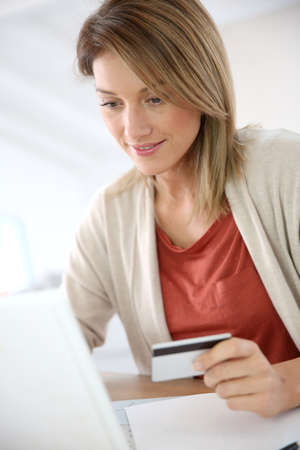 Cheerful middle-aged woman buying on internet Stock Photo - 25319708