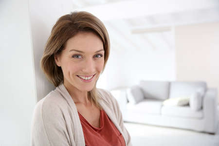 realestate: Middle-aged woman standing in modern home