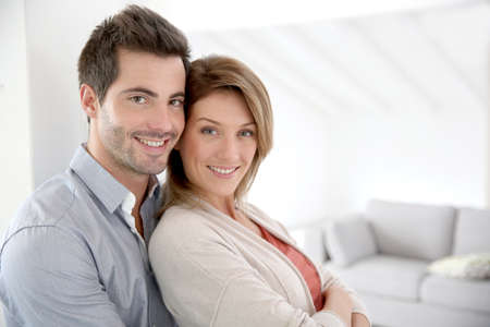 Couple standing in contemporary home Stock Photo