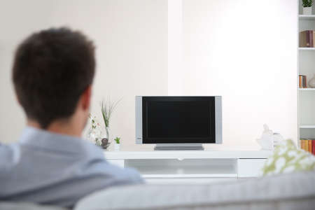 man watching tv: Back view of man in couch watching TV Stock Photo