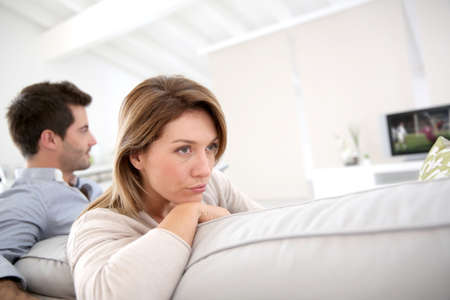 sad old woman: Couple disagreeing in the choice of TV program