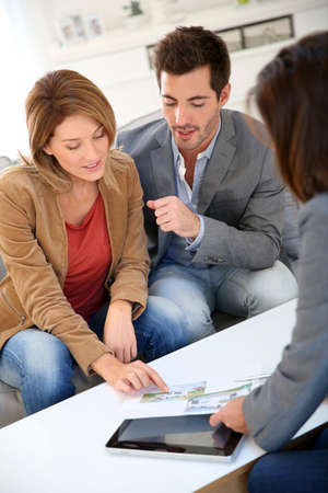 Couple meeting financial adviser for real estate project photo