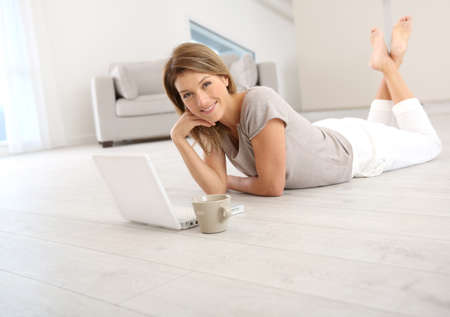 woman relaxing: Woman websurfing on the net with laptop