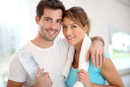 Portrait of smiling couple in fitness gym photo