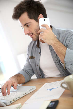working from home: Salesman working from home and talking on phone