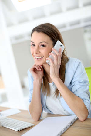 Saleswoman at work using smartphone