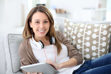 Smiling young woman websurfing with tablet at home photo