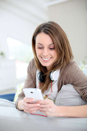 websurfing: Smiling young woman websurfing with smartphone Stock Photo
