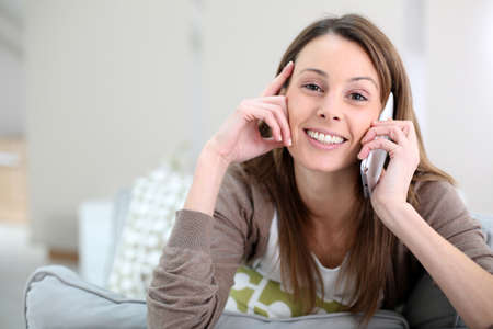 Smiling girl talking on mobile phone at home photo