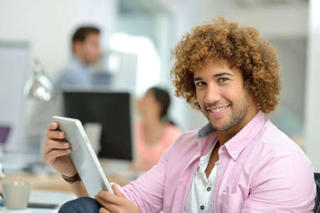Smiling man in office using digital tablet photo