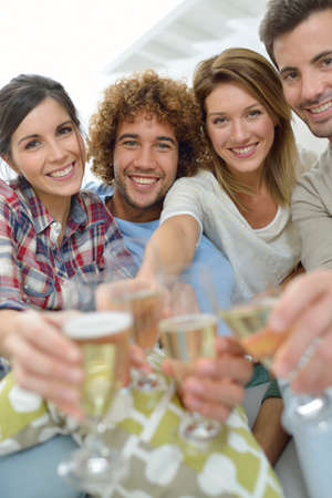 Closeup of friends cheering with glass of wine photo