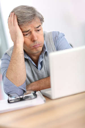 Businessman with worried expression while reading email photo