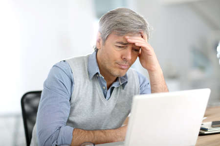 Senior businessman in front of laptop having a headache photo