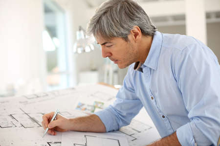 architect office: Architect working on construction blueprint in office