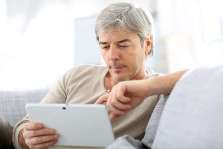 websurfing: Mature man in sofa websurfing with tablet