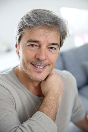 old sofa: Portrait of mature man relaxing at home in sofa