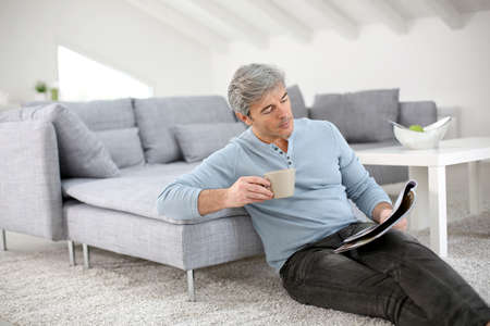 Senior relaxing at home and reading magazine