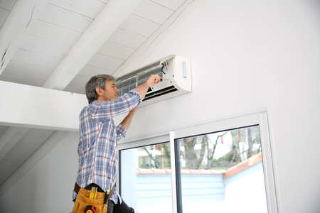 conditioner: Repairman fixing air conditioner unit