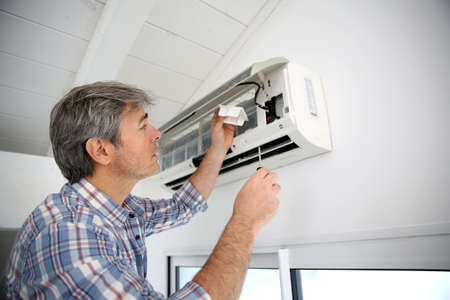 maintenance: Repairman fixing air conditioner unit
