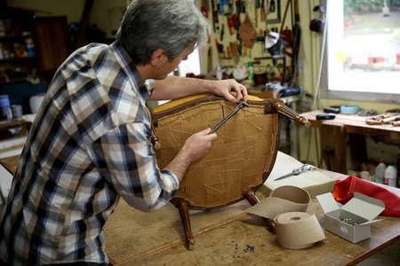 upholstery: Craftsman repairing antique armchair in workshop
