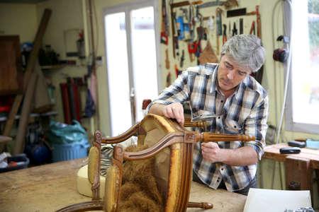 Vakman repareren van antieke leunstoel in workshop Stockfoto