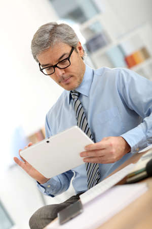 Senior businessman in office working on tablet photo