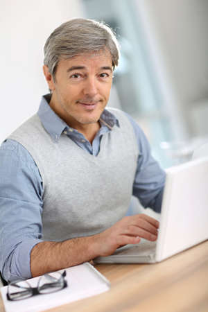 Senior businessman in office working on laptop photo
