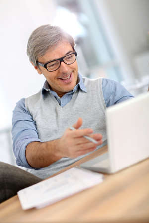 good news: Happy businessman reading good news on laptop Stock Photo