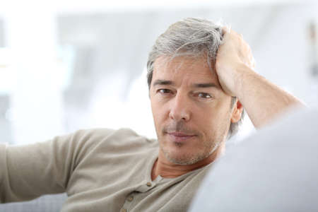 Portrait of attractive mature man relaxing at home photo
